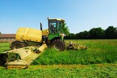 Weide van het tractor de scherpe gras Stock Fotografie