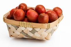 Weiden- Korb mit Kirsch-Tomaten Mini-kumakos geschnitten in halbes und in ganzes Mit Wassertropfen lizenzfreie abbildung