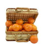 Weidenkasten gefüllt mit Tangerinen über Weiß Stockfotografie