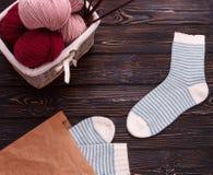 Weidenkorb füllte mit Wolle und Garn mit gestreiften weißen Socken auf einem dunklen hölzernen Hintergrund Lizenzfreies Stockfoto