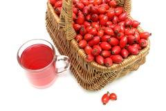 Weidenkorb mit Beeren von wildem Rosafarbenem und ein Getränk in einem Glas m Lizenzfreies Stockfoto