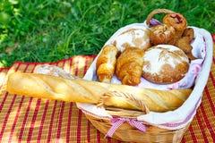Weidenkorb mit dem Brot, das auf dem Gras steht Stockfoto
