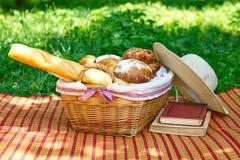 Weidenkorb mit dem Brot, das auf dem Gras steht Lizenzfreie Stockfotos