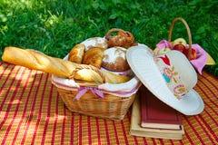 Weidenkorb mit dem Brot, das auf dem Gras steht Stockfotografie