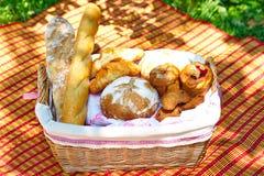 Weidenkorb mit dem Brot, das auf dem Gras steht Lizenzfreie Stockfotografie