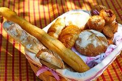 Weidenkorb mit dem Brot, das auf der Decke steht Stockbilder