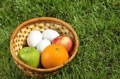 Weidenkorb mit Früchten und Eiern auf Gras Stockfotos