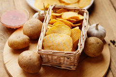 Weidenkorb mit Kartoffelchips, Kartoffel und Soße Stockfotografie