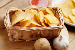 Weidenkorb mit Kartoffelchips, Kartoffel und Soße Lizenzfreies Stockfoto