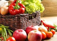 Weidenkorb mit Obst und Gemüse auf Holztisch Stockfotos