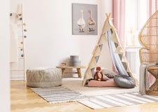 Weidenpfaustuhl nahe bei Zelt mit Kissen und Puff auf Skandinavier entwarfen das Spielzimmer des Mädchens, wirkliches Foto lizenzfreies stockfoto