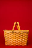 Weidenpicknickkorb auf einem roten Hintergrund Lizenzfreies Stockbild