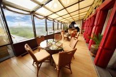 Weidenstühle und Glastabellen in der Gaststätte Stockbilder