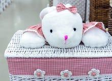 Weidenwäschekorb mit einem rosa Stoff und einem Spielzeug stockbild