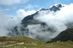 Weidestenen en berg tussen wolken nabijgelegen Sustenpass Stock Fotografie