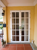 Weiße französische Türen des doppelten Patios mit Fenstern auf gelber Wand Stockfotos