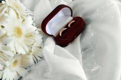 Weiße Gerbera- und Hochzeitsringe Stockbilder