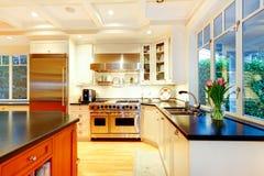 Weiße große Luxusküche mit enormem Ofen und Kühlschrank. Stockfotos