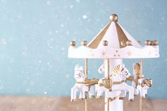 Weiße Karussellpferde der alten Weinlese auf Holztisch Retro- gefiltertes Bild mit Funkelnüberlagerung Lizenzfreie Stockfotos
