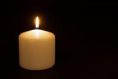 Weiße Kerze, die gegen einen schwarzen Hintergrund brennt Lizenzfreie Stockbilder