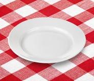 Weiße leere Platte auf roter Ginghamtischdecke Stockfoto