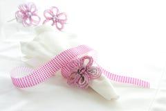 Weiße Leinenserviette mit rosafarbenem wulstigem Serviettering Stockfoto
