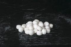 Weiße Naphthalinbälle auf schwarzem Samt Stockfoto