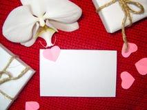 Weiße Orchidee und Geschenkbox auf einem roten Hintergrund, Valentinsgruß-Tageshintergrund Kleine Papierherzen Lizenzfreie Stockfotos