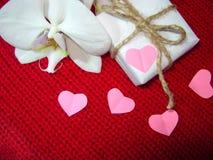 Weiße Orchidee und Geschenkbox auf einem roten Hintergrund, Valentinsgruß-Tageshintergrund Kleine Papierherzen Lizenzfreie Stockfotografie