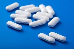 Weiße Pillen über Blau Stockfotos