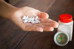 Weiße Pillenmedizinkopfschmerzen an Hand Stockfoto