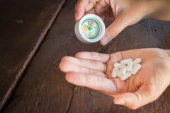 Weiße Pillenmedizinkopfschmerzen an Hand Lizenzfreie Stockfotos