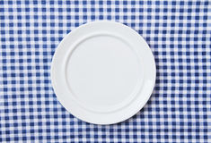 Weiße Platte auf blauem und weißem checkered Gewebe Stockfoto