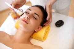 Weiße Schablone mit Gurke auf Frauengesicht Frau im Schönheits-Salon erhält Marine Mask Lizenzfreies Stockfoto