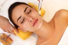Weiße Schablone mit Gurke auf Frauengesicht Frau im Schönheits-Salon erhält Marine Mask Stockfoto