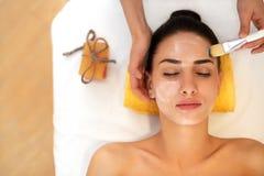 Weiße Schablone mit Gurke auf Frauengesicht Frau im Schönheits-Salon erhält Marine Mask Stockbild