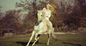 Weißer Engel, der ein Reinweißpferd reitet Stockfotos