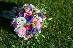 Weißer Hochzeitsblumenstrauß, der auf grünem Gras liegt Lizenzfreies Stockbild