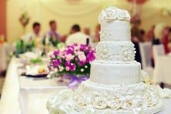 Weißer Hochzeitskuchen auf Innenhintergrund Stockfotos