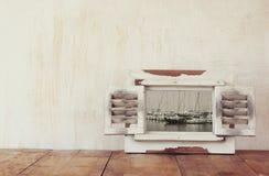 Weißer Holzrahmen der Weinlese mit dekorativem Schwarzweiss-Foto des Jachthafens mit Yachten Stockfoto