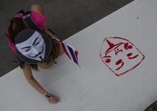 Weißer Maske Protestor, der thailändische Flaggenfarben auf Fahne hält Stockfotografie