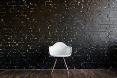 Weißer Stuhl, der im Raum auf braunem Bretterboden über schwarzer Backsteinmauer steht Lizenzfreie Stockbilder