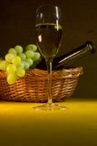 Weißer Wein in einem Glas und in den Trauben Stockfotografie