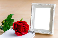 Weißer Weinlesefotorahmen und Rotrose mit leerem Tagebuch Lizenzfreie Stockbilder