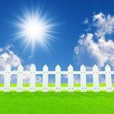 Weißer Zaun auf einem Sommerrasen Lizenzfreie Stockfotos