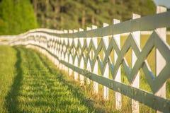 Weißer Zaun, der zu einer großen roten Scheune führt Lizenzfreies Stockfoto