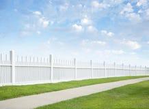 Weißer Zaun, Gras, Bürgersteig, blauer Himmel und Wolken Lizenzfreie Stockfotografie