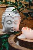 Weißes Buddha-Porträt in der Meditation mit brennender Kerze, Grün lässt Ruscusblumen auf rustikalem hölzernem Wandhintergrund Ge Lizenzfreies Stockfoto