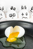 Weißes Ei eingelaufen Bratpfanne mit Eiern mit den Gesichtern erschrocken Lizenzfreies Stockfoto