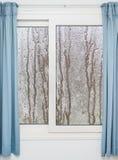 Weißes Fenster mit blauen Vorhängen an einem regnerischen Tag Lizenzfreie Stockbilder